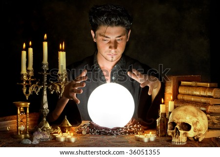 Halloween scene of a young sorcerer and his crystal ball - stock photo