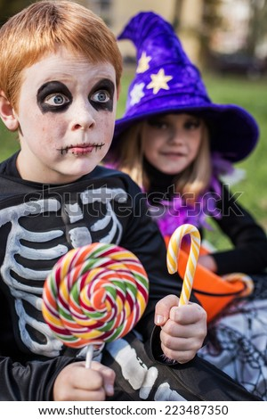 Halloween. Skeleton and witch holding colorful candies. Outdoor portrait  - stock photo