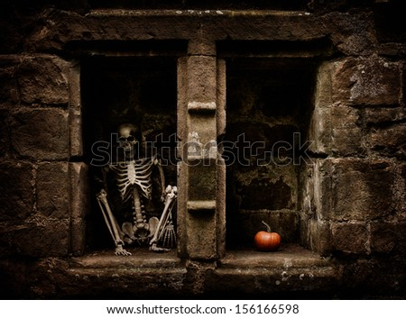 Halloween skeleton sitting in a graveyard alcove - stock photo