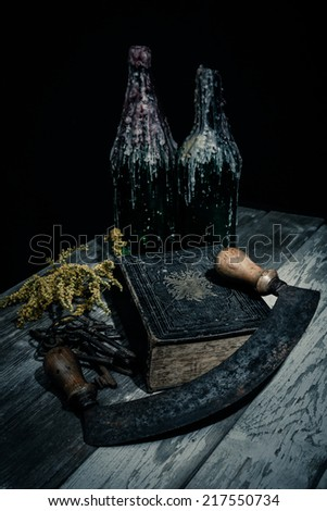 halloween still-life a bibel, a sickle and two bottels with candle tracks in the dark on a wooden table - stock photo