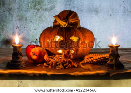 Halloween still life with pumpkins, apple, candles and rosary - stock photo