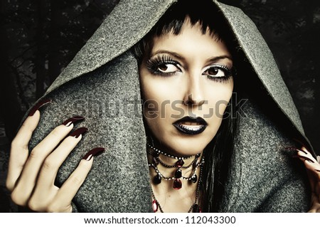 Halloween style - costume and make up of sexy evil witch - stock photo