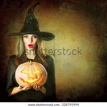 Halloween Surprised Witch with a magic Pumpkin. Beautiful young woman in witches hat and costume holding carved Jack lantern pumpkin. Halloween art design