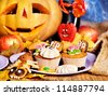 Halloween table with trick or treat. Carving pumpkin. - stock photo