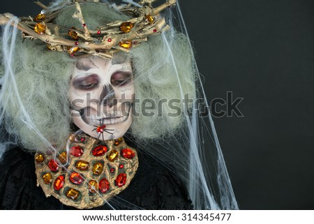 Halloween. The art of makeup girl for the carnival of death, skeleton, ghosts, cobwebs and decorations on black background