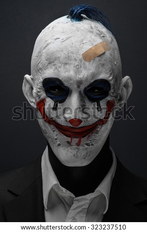 Halloween theme: Crazy terrible blue clown in black suit isolated on a dark background in the studio