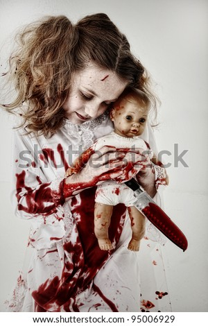 Halloween Theme Girl Child Zombie or Ghost covered in blood holding knife and baby doll. - stock photo