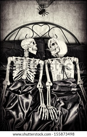 Halloween theme.  Two skeletons in bed together. Textured. - stock photo