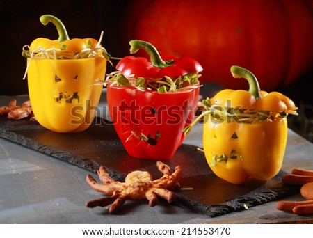 Halloween themed salad with stuffed red and yellow sweet peppers with cutout faces like jack-o-lanterns served with a flying bat pastry on a curved bark plate - stock photo