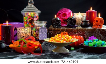 Halloween trick or treat party table with bowls and apothecary jars of candy with skull candles against a black background