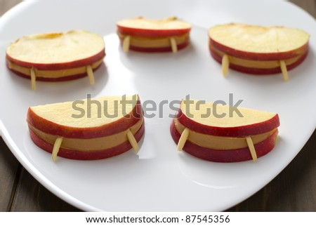 Halloween vampire apple lips in a plate on a wooden table - stock photo