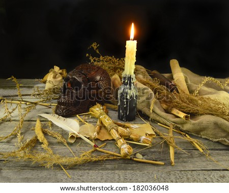 Halloween voodoo still life with burning candle, skull and straw doll - stock photo