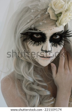 Halloween witch. Beautiful woman wearing santa muerte mask and wedding dress