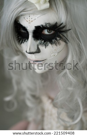 Halloween witch. Beautiful woman wearing santa muerte mask portrait - stock photo