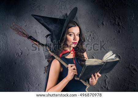 Halloween Witch. Beautiful young woman in witches hat and costume holding  pumpkin magic broom