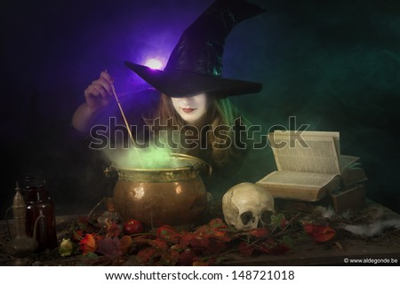 halloween witch boiling a potion in a caldron - stock photo