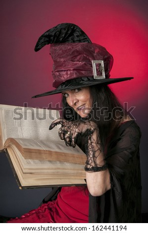 Halloween witch casting spells on red background