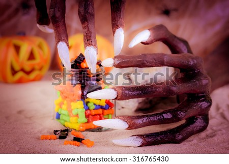 Halloween witch hands and colorful sweets close up - stock photo