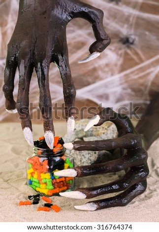 Halloween witch hands reaching for the colorful candies  - stock photo