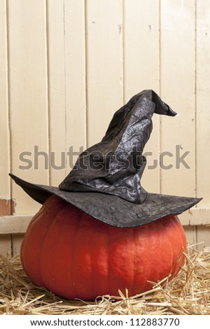 halloween witch hat on pumpkin lying on straw - stock photo