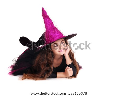 halloween witch in pink hat  lying on the floor looking to the copy space area