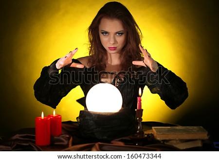Halloween witch on dark yellow background - stock photo