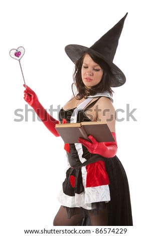 Halloween witch reads magic book - stock photo