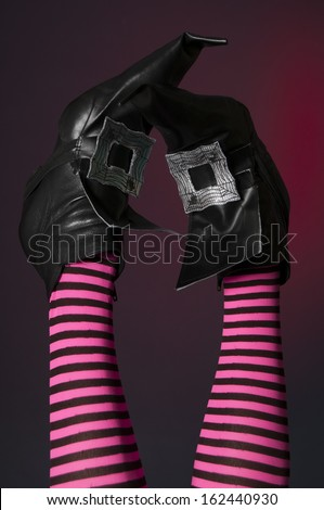 Halloween witch's feet and legs upside down with stripey pink and black tights on red background