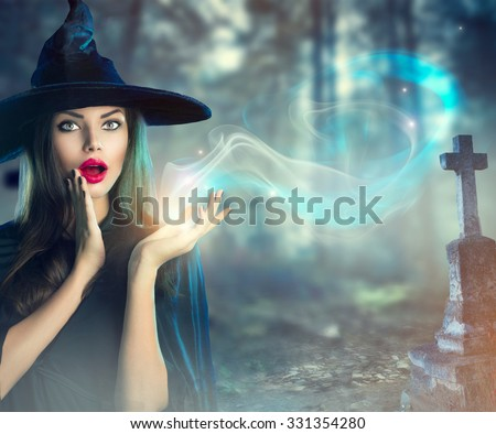 Halloween Witch with a magic in a dark Old Spooky cemetery. Beautiful young woman in witches hat and costume holding magical light in her hand. Halloween art design - stock photo
