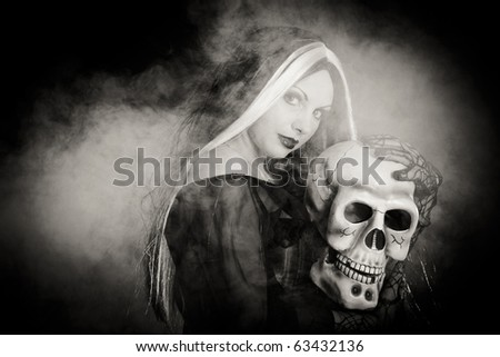 Halloween witch with a skull over black background with smoke. Black and white - stock photo