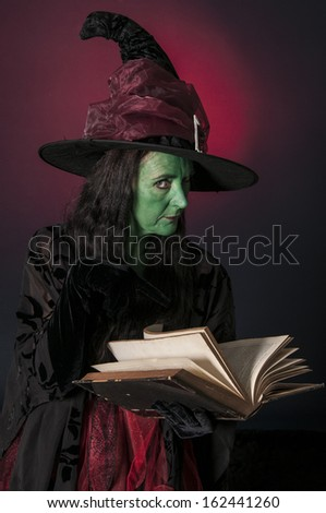 Halloween witch with book of spells on red background
