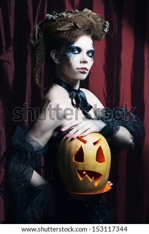 Halloween witch with  carved pumpkin over red  background.  - stock photo
