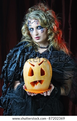 Halloween witch with  carved pumpkin over red  background.