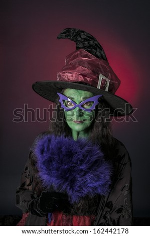 Halloween witch with green face and purple glasses on red background