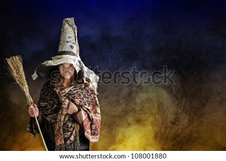 halloween witch with hat and broom, smoke and fire background - stock photo