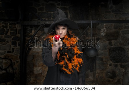 halloween witch with poisoned apple, in an old kitchen - stock photo