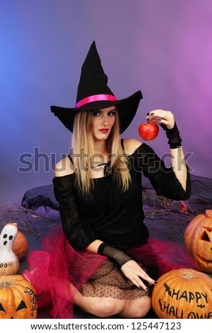 Halloween witch with red apple on color background