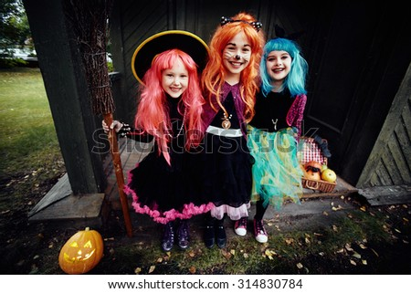 Halloween witches looking at camera by haunted house - stock photo