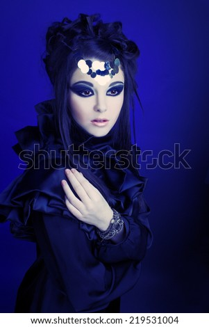 Halloween woman in black dress with artistic visage with smokey-eyes - stock photo