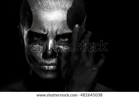 Halloween. Woman in day of the dead mask skull face art. Halloween face art on black background. Halloween make up
