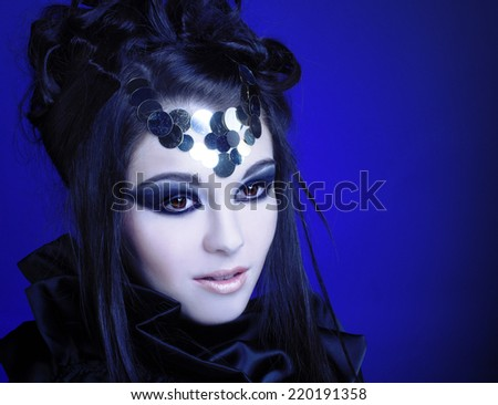 Halloween. Young woman in black dress with artistic visage with smokey-eyes