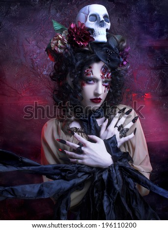 Halloween. Young woman in witch image with bloody makeup ann with skull. - stock photo