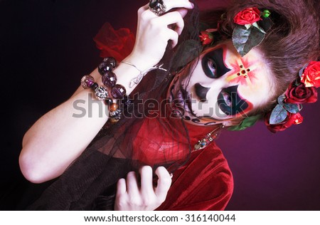 Halloween. Young woman with creative visage and with roses in her hair.