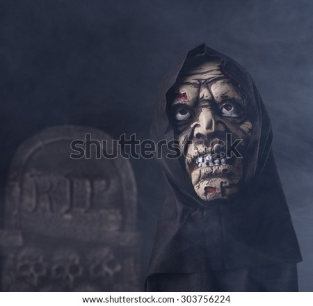 Halloween zombie prop on a dark smoky background with a tombstone - stock photo