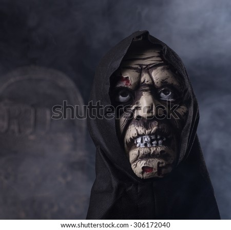 Halloween zombie prop on a dark smoky background with a tombstone