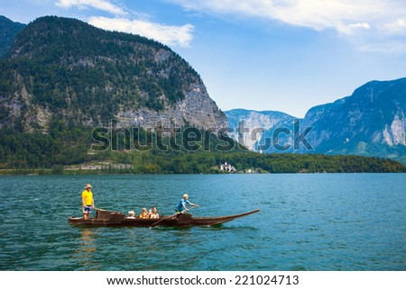 Hallstatt, Austria - August 7, 2013: People crossing the lake with a traditional boat typical for Hallstatt village, Austria