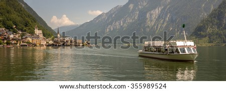 Hallstatt Scenic picture-postcard view of famous mountain village by Lake Hallstatt and Ferry boat with Austrian Flag in the Austrian Alps under Golden Dramatic Sky Sunset in Summer, Austria