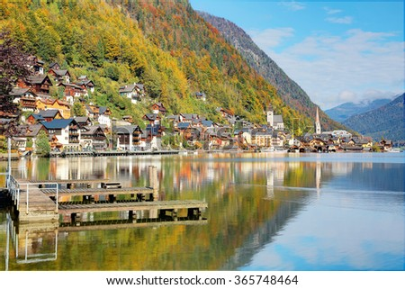 Hallstatt under blue sunny sky, with beautiful reflections on smooth lake water in brisk colorful autumn season ~ Scenery of an amazing lakeside village in Salzkammergut region of Austria, Europe - stock photo