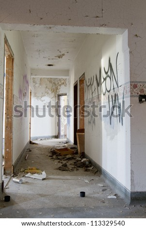 Hallway in an abandoned building covered with graffiti. - stock photo