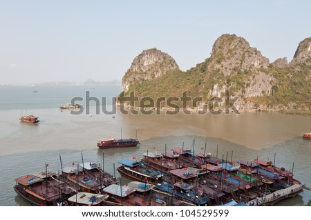 HALONG BAY, VIETNAM - APRIL 10: Cruising boats on April 10, 2011 in Halong Bay, Vietnam serving tourists to discover a 1553 sq. km UNESCO World Heritage Site consisting of 1169 islets of various size.
